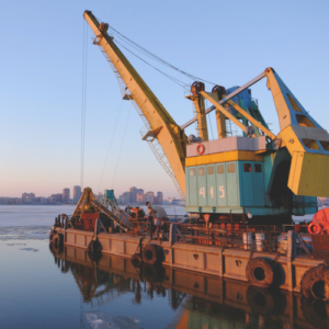 Leased Crane on dock in harbor with cityscape in the distance