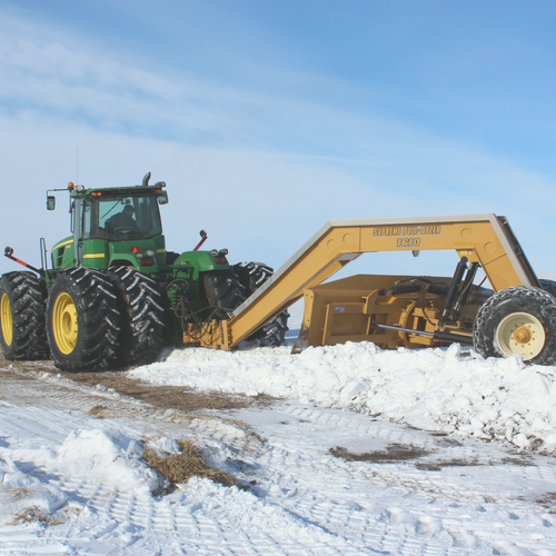 Leased Supreme Pull-Dozer attached to large tractor moving snow
